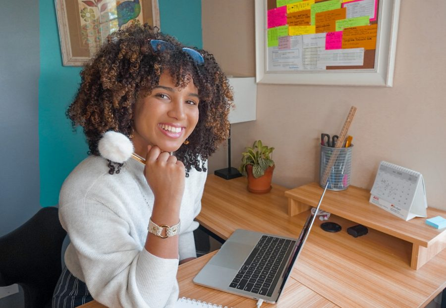 Gabby, a young Black woman with curly brown hair, sitting at a desk in front of her computer while holding a pen and smiling while angling her body to face the the camera.